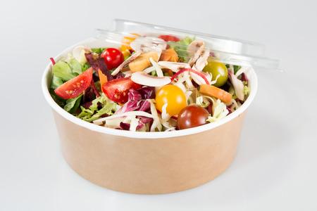 Ensalada verde mixta orgánica fresca con calabaza en caja de cartón kraft
