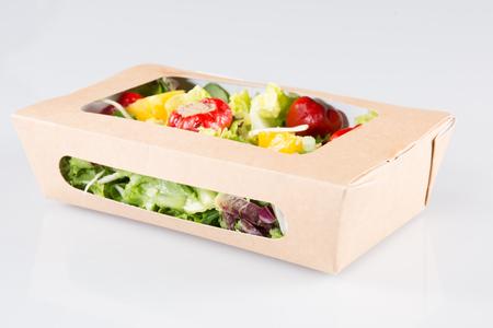 comida rápida con ensalada en una caja sobre un fondo blanco