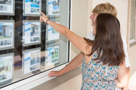 Junge Paare der Seitenansicht, die Fensteranzeige Immobilienbüro im strret betrachten