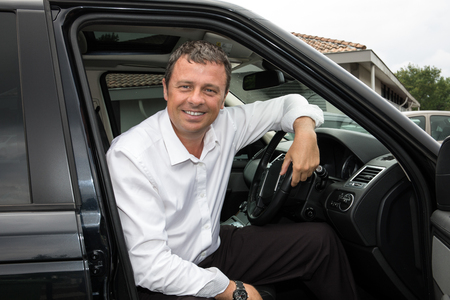 cheerful businessman gets into his car in england