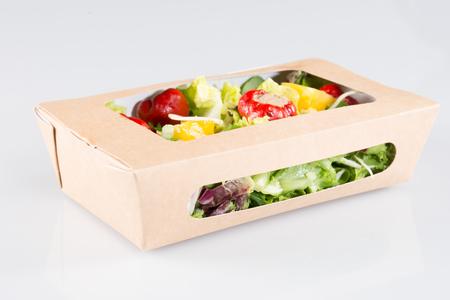 Comida rápida con ensalada en una caja sobre un fondo blanco.