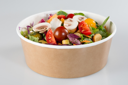 ensalada tradicional en un recipiente de cartón aislado en un fondo blanco