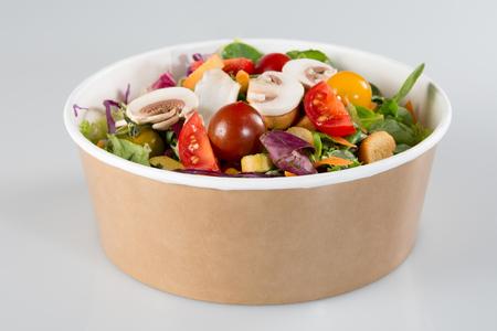salade traditionnelle dans un récipient en carton isolé sur un fond blanc