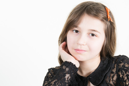 10 year old girl portrait with serious face on a white background