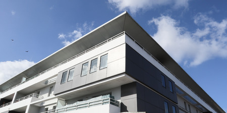 White facade of a modern apartment building with windows and different black accents Stock Photo
