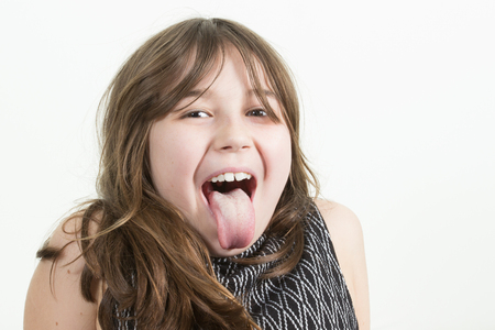 Angry little girl shows her tongue in funny grimace Stock Photo
