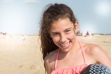 Summer lifestyle happy smiling portrait of pretty young curly girl having fun on the beach Standard-Bild