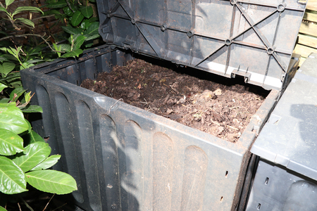 Compost bin in the garden for Composting pile of rotting kitchen fruits and vegetable scraps Stock Photo