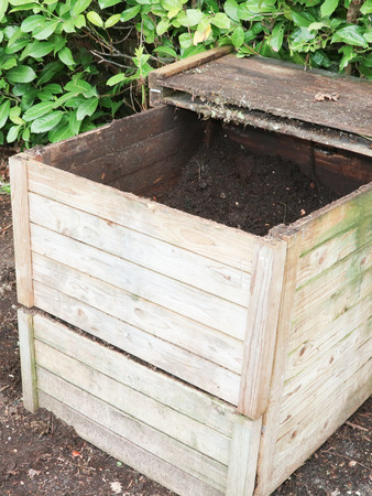 wood Compost bin in the grass next to vegetable garden Stock Photo