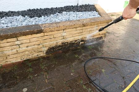 Hombre limpiando la pared con limpiador de alta presión en primer plano