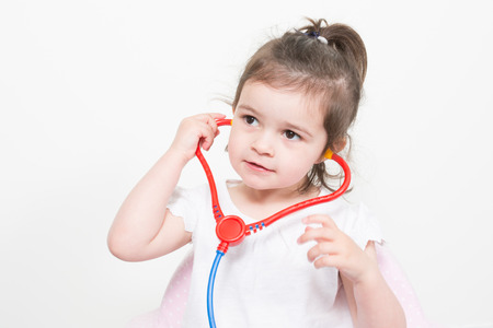 Smiling little girl playing doctor with stethoscope isolated on white Stok Fotoğraf