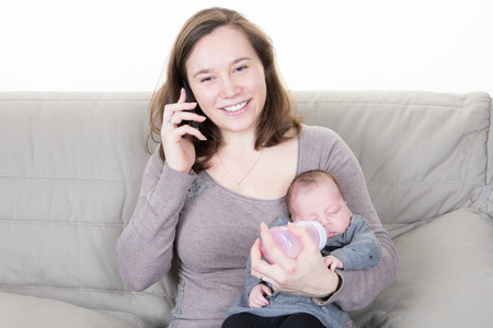 mother gives the bottle to her new born baby while restoring to her mobile phone on the sofa of the living room