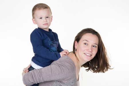 young boy in blue tshirt piggyback on the shoulders of his mother plays