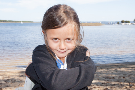 sad child girl who pouted on the sand beach summer day Stock Photo