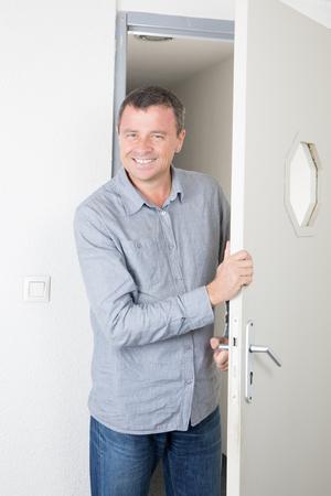 Handsome young businessman entering the door in office