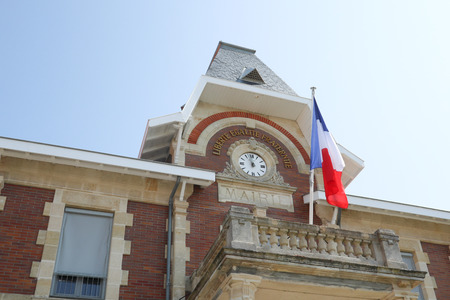 city clock attached to the town hall with french flag in cityhall Banco de Imagens
