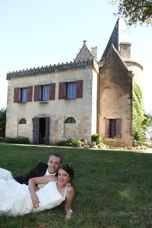 young married couple in wedding clothes lying on grass