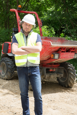 man manager in front of an excavator on construction site