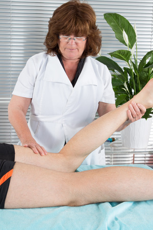 Sports massage by woman Physical therapyst massaging leg of young male athelete