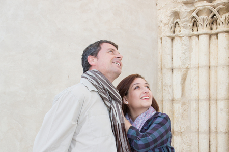 Woman traveler standing with a man in a street looking at somethings upwards Stock Photo