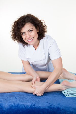 masseuse woman performs a massage on her pretty athletic slim client