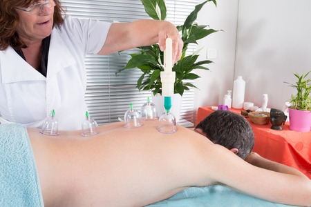 man back massage with suction cup by senior woman
