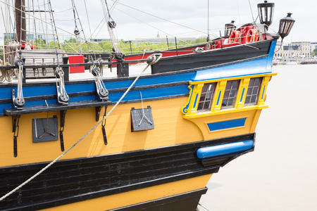 a view from the rear of a yellow and blue replica vessel sails boat