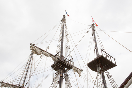 Vintage design of part of an old wooden ship masts and ropes of ancient vessel with cloudy sky