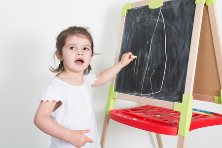 child girl makes chalk drawings on a chalkboard toys