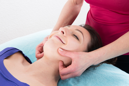 face massage of a beautiful woman at the wellness center and spa