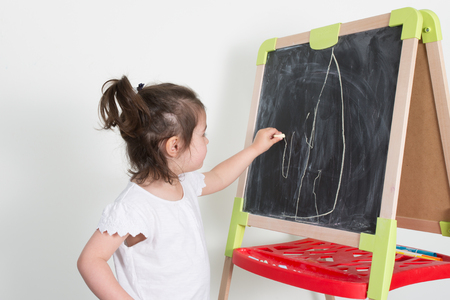 young child girl makes a chalk drawing on the blackboard in toy Archivio Fotografico