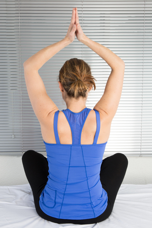 Young fit woman meditates while practicing yoga