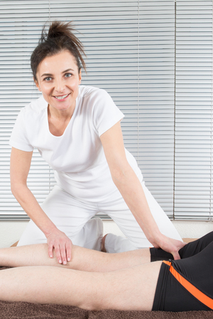 Physical woman therapyst massaging leg of young man athelete