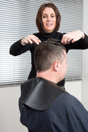 woman hairdresser cuts the hair of a handsome man at the hairdressing salon Banque d'images
