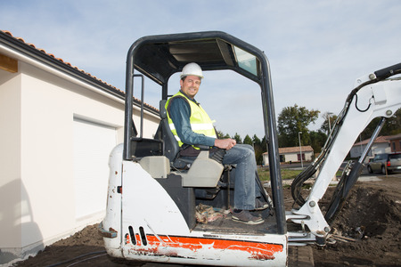 handsome man sitting on buldozer digger on house construction site