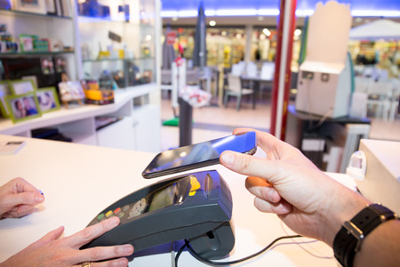 Man paying bill through smartphone using NFC technology mobile payment Banque d'images