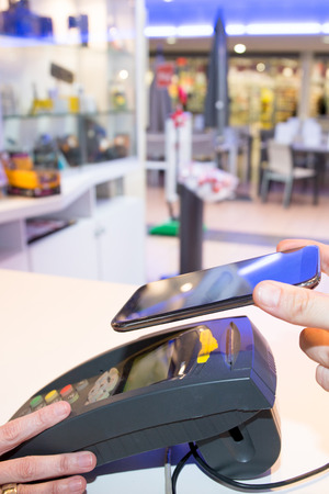 man making payment for purchase transaction with his mobile phone contactless Nfc Banque d'images