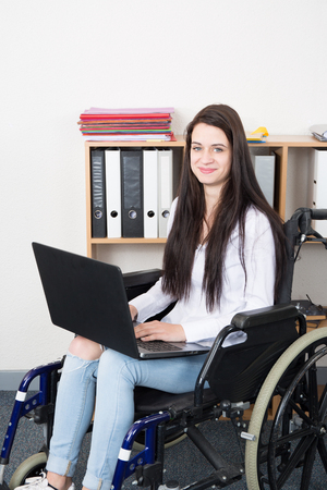 beautiful female office worker in wheelchair holding a laptop and smiling at camera