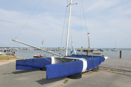 catamaran boat resting on the port wrapped in blue blanket to protect it Standard-Bild