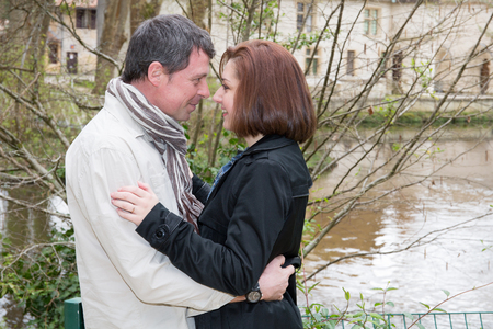 beautiful couple kiss facing each other in the eye near city lake river
