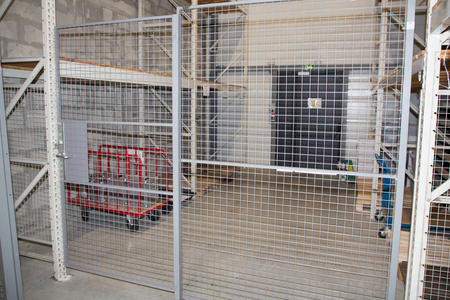 security storage with racks and a metal locked door warehouse Stock Photo