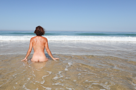 single alone woman naked in nudist beach in back view during summer vacation Banque d'images - 106629615