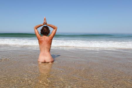 naked nudist woman sit water on empty beach yoga meditating