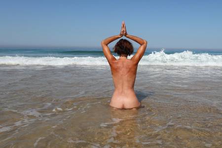 nudist naked woman make yoga bath in sea