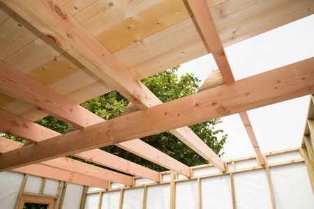 Installation of wooden beams at construction roof truss system of house