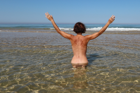 a woman with her arms in the air sitting in the water of the sea seen from behind and naked Stock Photo
