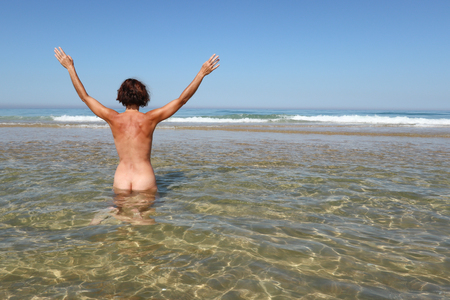 happy nudist woman sit on beach sea water