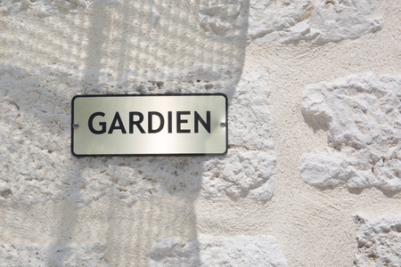 french sign on building outdoor gardien means guardian concierge service in french