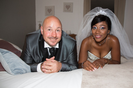 interracial couple african caucasian american bride and groom lying on bed at home in wedding day