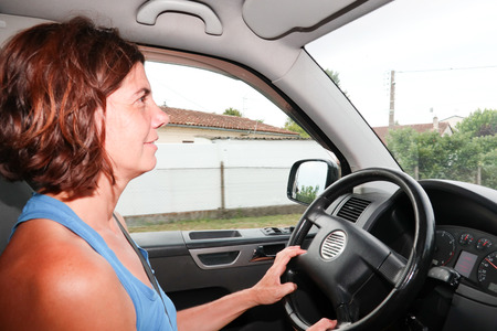 forties middle aged woman driver in car van in summer day 免版税图像